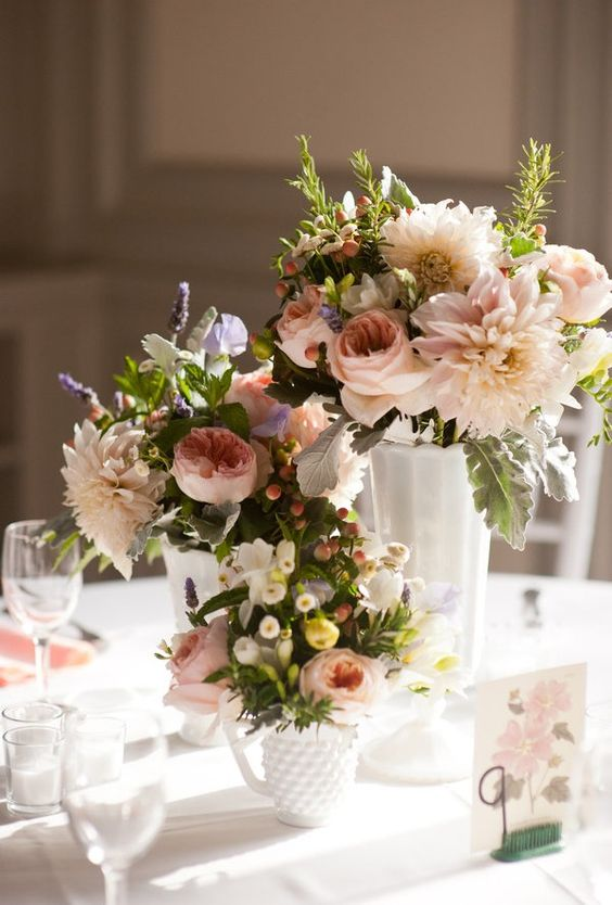 a chic cluster wedding centerpiece of white vases and mugs, with pastel blooms, berries and greenery