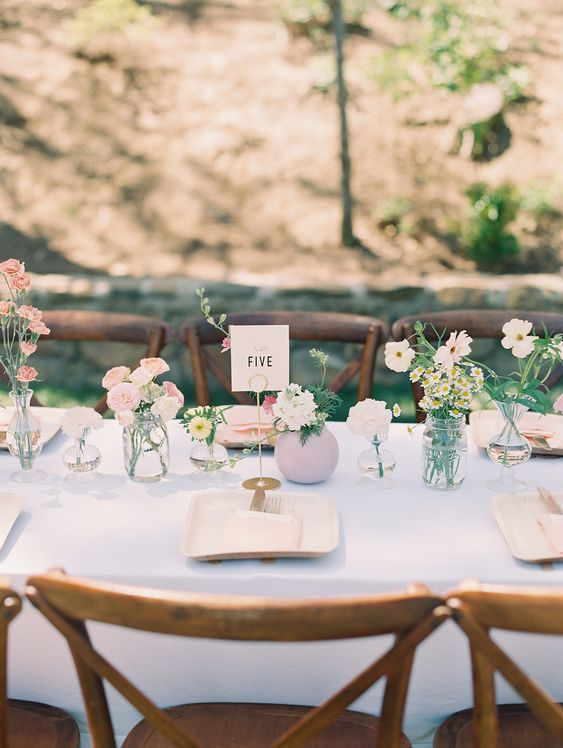 a cluster wedding centerpiece of bud vases, with pastel and white blooms and greenery is very chic