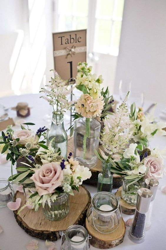a cluster wedding centerpiece of wood slices, white and pastel blooms, greenery, candles and a table number