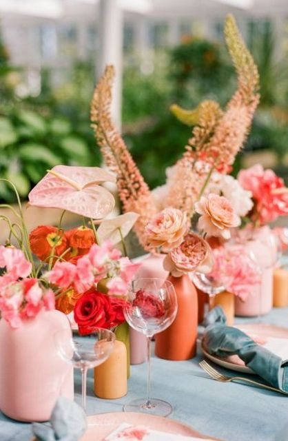 a colorful cluster wedding centerpiece with bright matte vases, pink, orange and red blooms and greenery