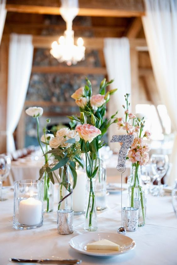 a delicate cluster wedding centerpiece of sheer bud vases and bottles, pink and white blooms and candles
