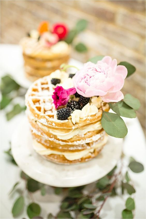 a delicious waffle wedding cake with blackberries, cream and a large pink peony on top