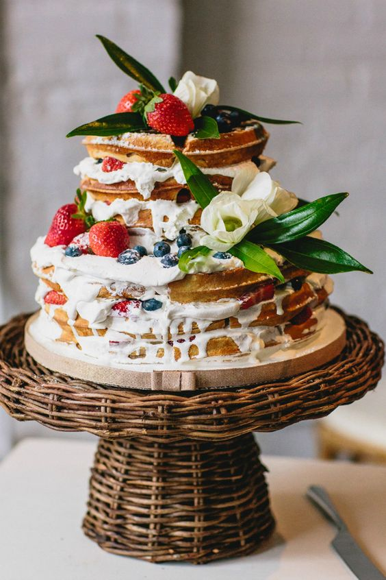 a delicious waffle wedding cake with cream drip, fresh berries, foliage and white blooms is very summer-like