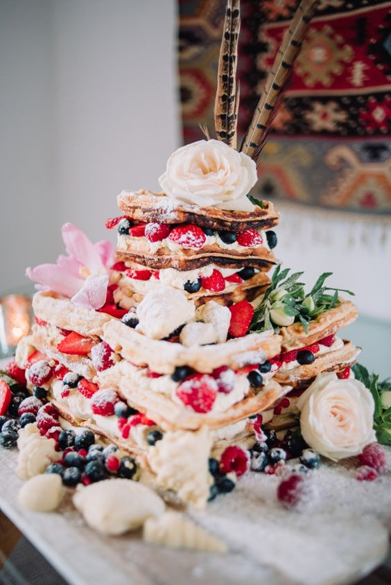 a gorgeous summer boho wedding cake with fresh berries, pink and white blooms, greenery and feathers on top