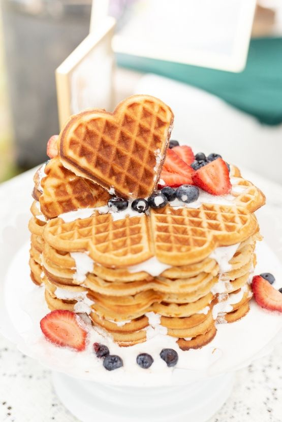 a heart-shaped waffle wedding cake topped with blueberries and strawberries is a tasty and cool dessert