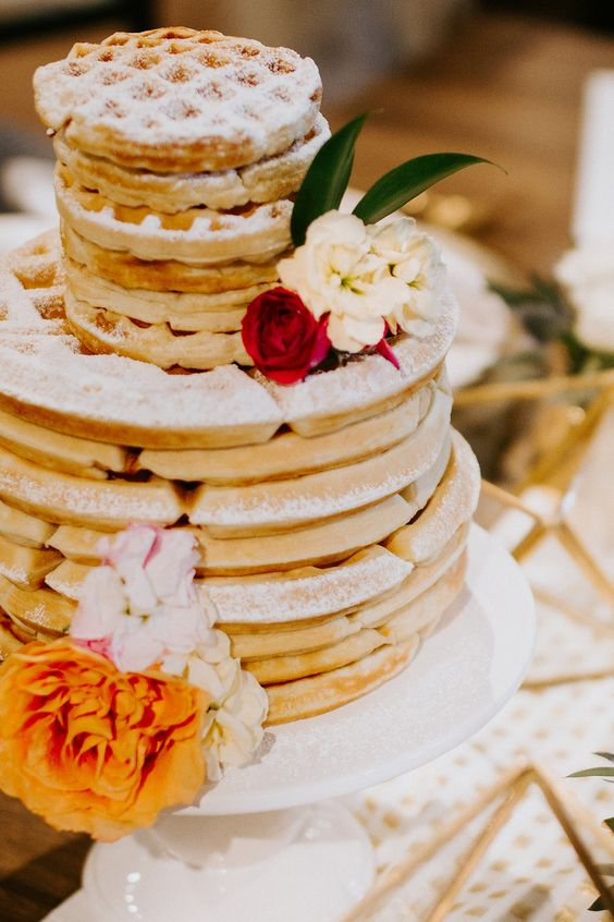 a lovely and simple waffle wedding cake with white and red blooms and foliage is a cool idea