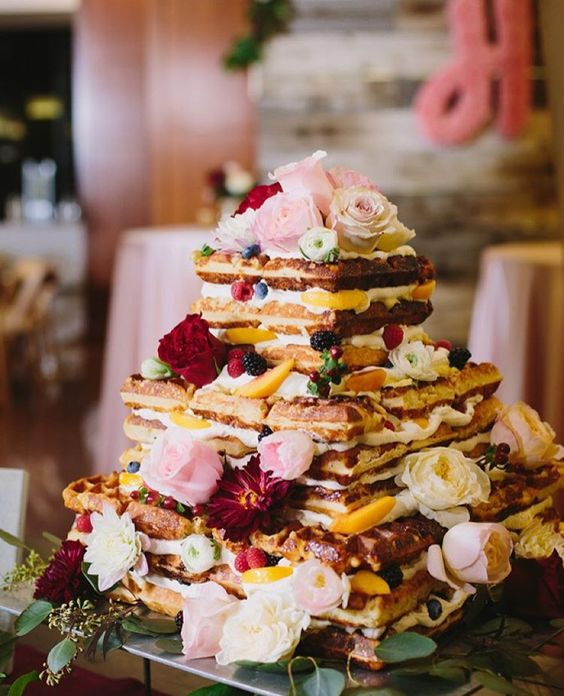a lovely waffle wedding cake with fresh burgundy and pink blooms, berries and peach slices for a summer wedding