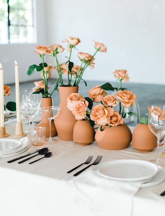 a modern cluster wedding centerpiece of terracotta vases and peachy roses looks bold and chic