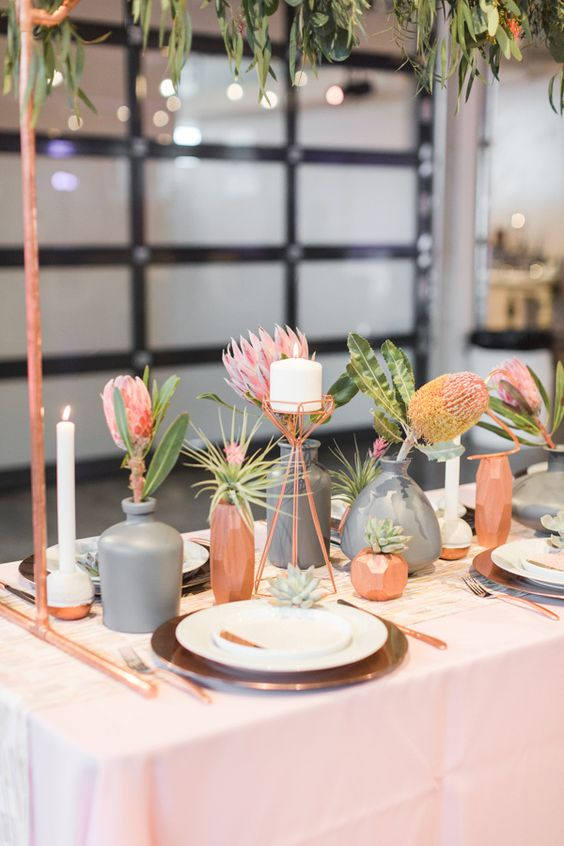 a modern cluster wedding centerpiece with copper and grey vases, bold pink blooms and greenery and candles