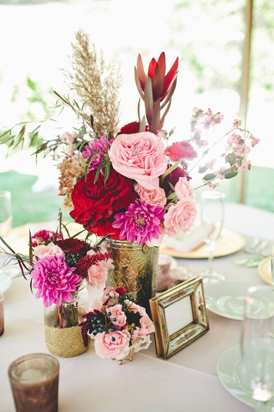 a refined cluster wedding centerpiece of gold vases, pink, fuchsia and burgundy blooms and greenery