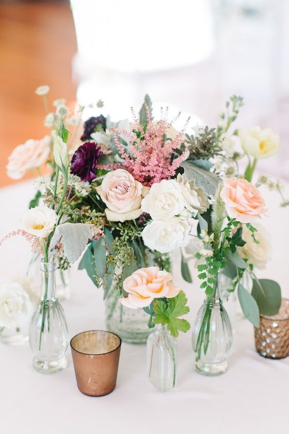 a romantic cluster wedding centerpiece of greenery, blush, white and pink blooms and some candles