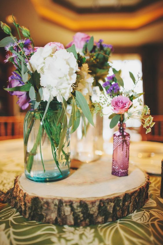 a rustic cluster wedding centerpiece of a wood slice, some jars and colorful and white blooms looks cool