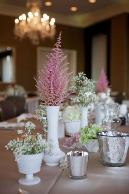 a rustic cluter wedding centerpiece of white vases, white, pink and green blooms and candles
