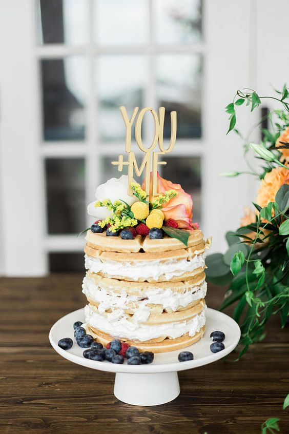 a small and delicious wedding cake with blueberries and raspberries, with pastel blooms and a cute and romantic topper