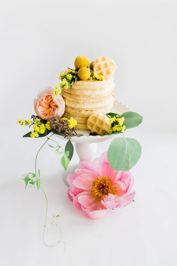 a small waffle wedding cake with yellow and pink blooms and greenery for a bright summer wedding