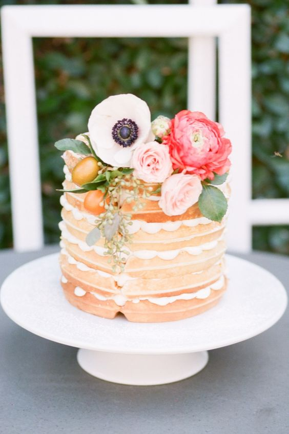 a small yet cute waffle wedding cake with pink and coral blooms, foliage and kumquats for a spring wedding