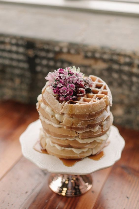 a small yet lovely waffle wedding cake with cream and some raspberries and pink blooms on top is amazing