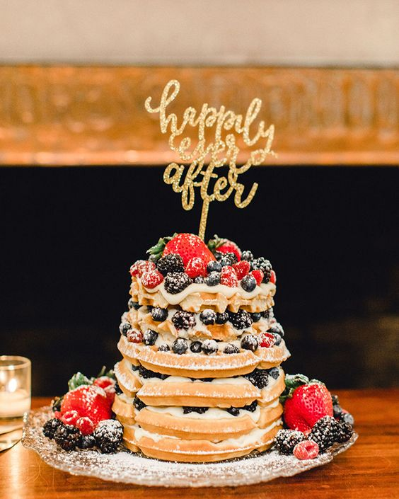 a small yet very tasty waffle wedding cake with strawberries, raspberries, blueberries and blackberries plus a glitter topper