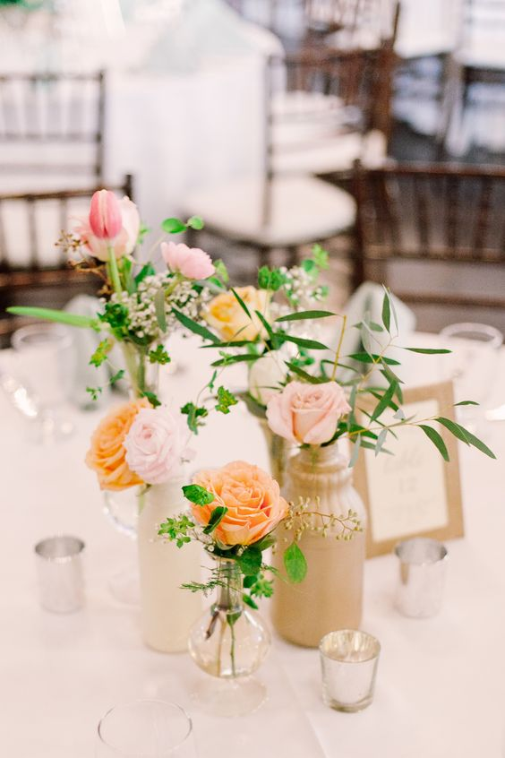 a stylish cluster wedding centerpiece with neutral and sheer vases, blush, pink, peachy blooms and greenery