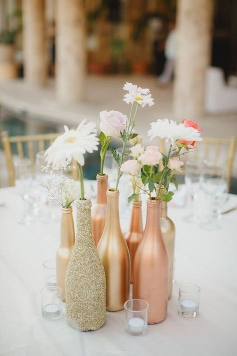 a very simple cluster wedding centerpiece of gold and copper bottles, white and pink flowers and greenery