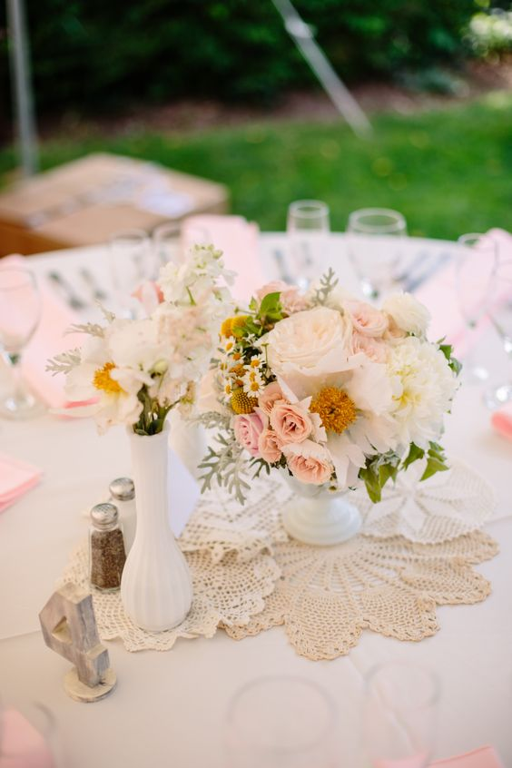 a vintage-inspired cluster wedding centerpiece of white vases, white and blush blooms and pale greenery