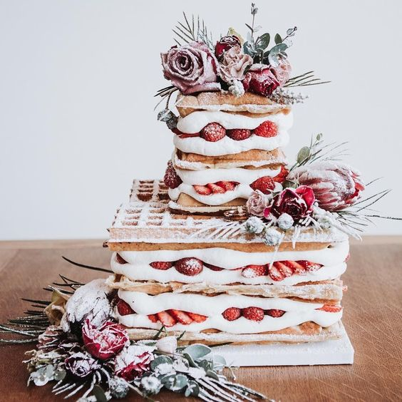 a waffle wedding cake with fresh strawberries and raspberries, greenery and pink and red blooms