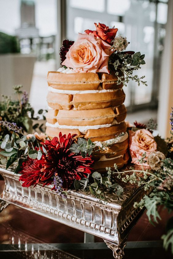 a waffle wedding cake with meringues and pink and burgundy blooms on top for a fall boho wedding