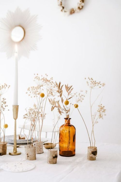 an ethereal wedding centerpiece of dried branches and billy balls inserted into wood pieces and apothecary bottles