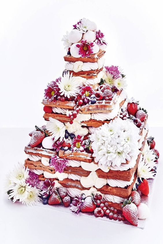 an oversized waffle wedding cake with various types of berries, white and pink blooms and some meringues