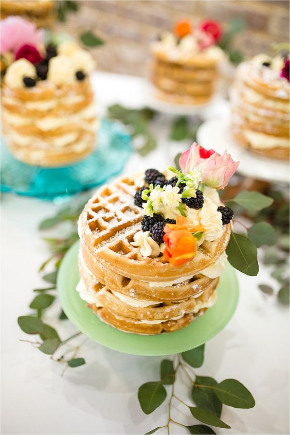 several mini Belgian waffle cakes with whipped cream, blackberries and pink blooms on top