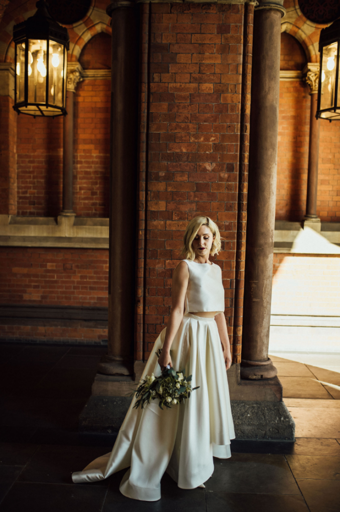 The bride was wearing a minimalist wedding separate with a sleeveless crop top and a high low full skirt with a train