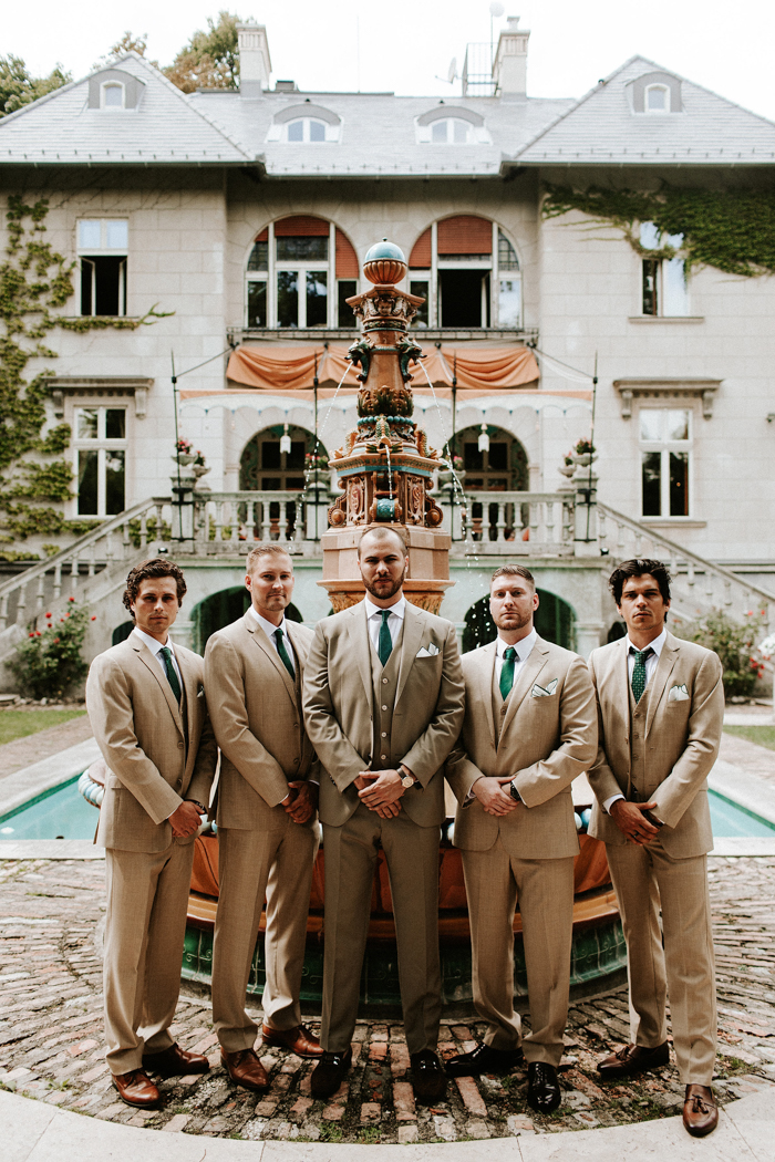 The groom and groomsmen were rocking tan-colored three-piece suits with emerald ties