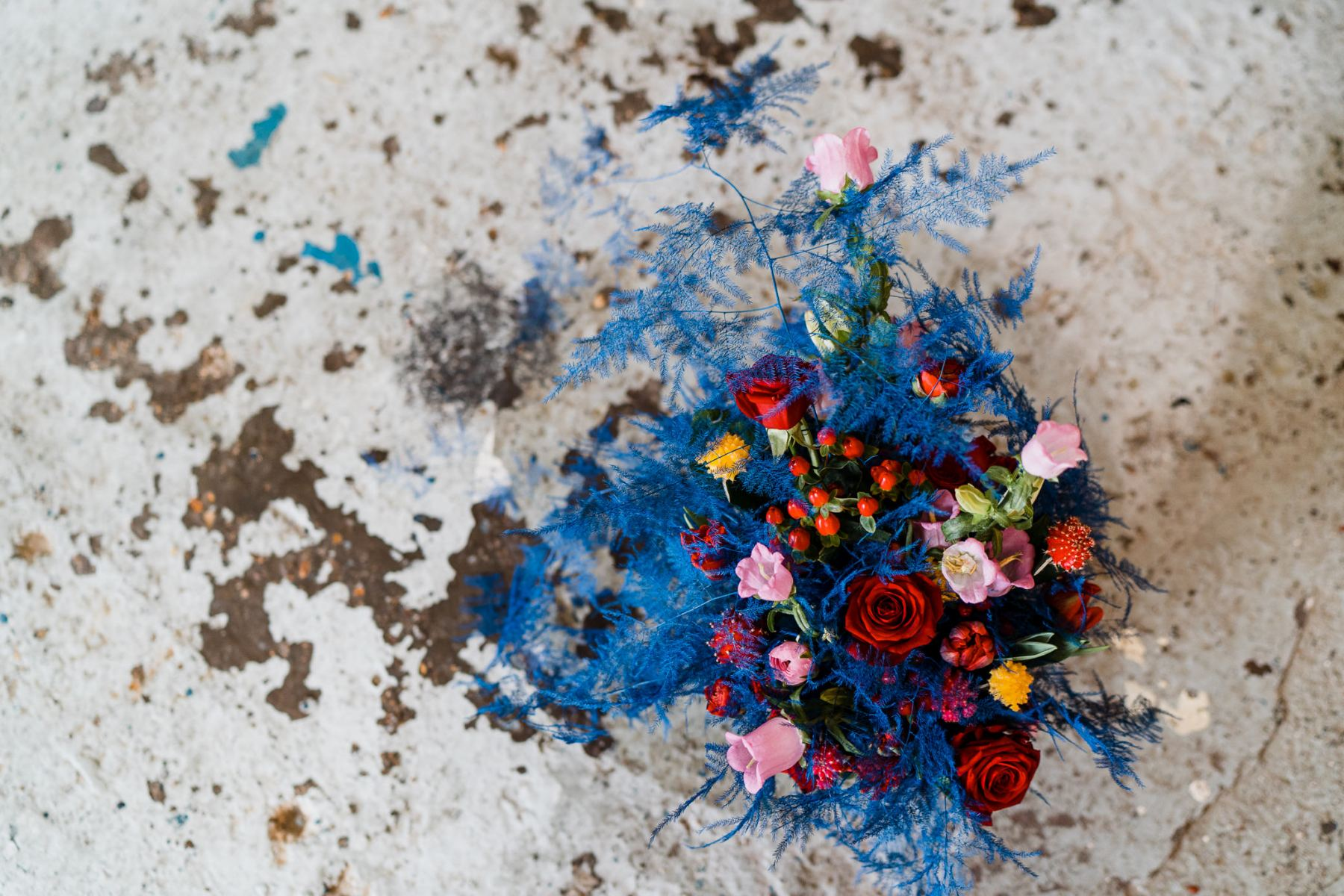 The wedding bouquet was done with super bright blooms of all colors, with berries and blue leaves