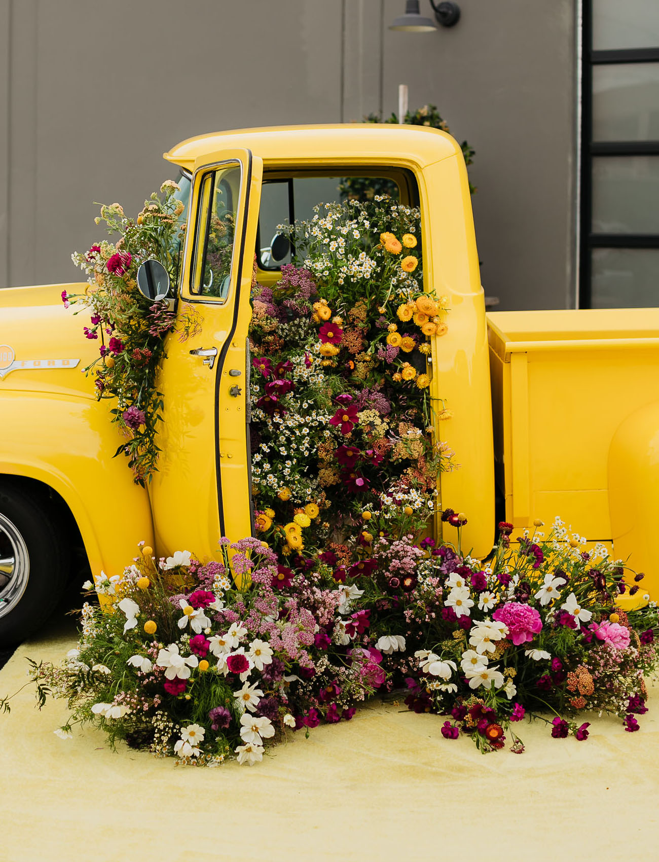 This gorgeous yellow truck was filled with bright blooms to make a statement decoration for this modern wedding shoot
