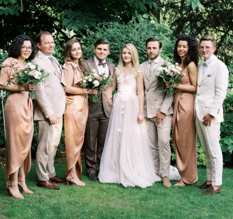 The bride was wearing a blush wedding dress with butterfly appliques, the groom was wearing a brown three-piece suit, the groomsmen were rocking neutral suits, the bridesmaids were wearing amber silk dresses