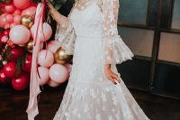 03 The bride was wearing a lace applique A-line wedding dress with an illusion neckline and bell sleeves