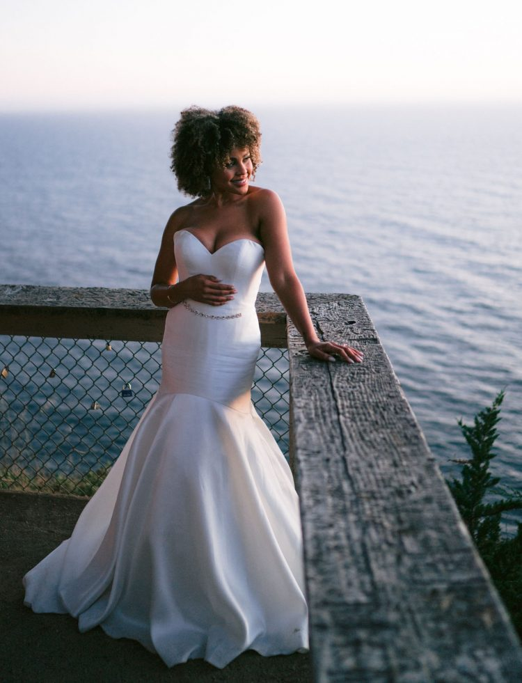 The bride was wearing a strapless mermaid wedding dress with an embellished sash and rocking her Afro hair