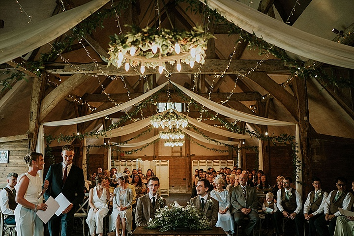The ceremony space was decorated with greenery, greenery chandeliers, white blooms