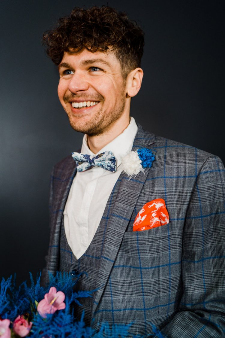 The groom was wearing a plaid grey three-piece suit, a botanical print bow tie and a colorful boutonniere
