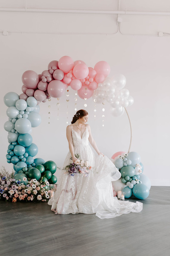 The wedding arch was done with ombre balloons - form white to blue and green, pastel blooms and celetial pieces hanging