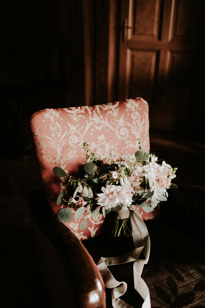 The wedding bouquet was composed of blush blooms and greenery and secured with grey ribbons