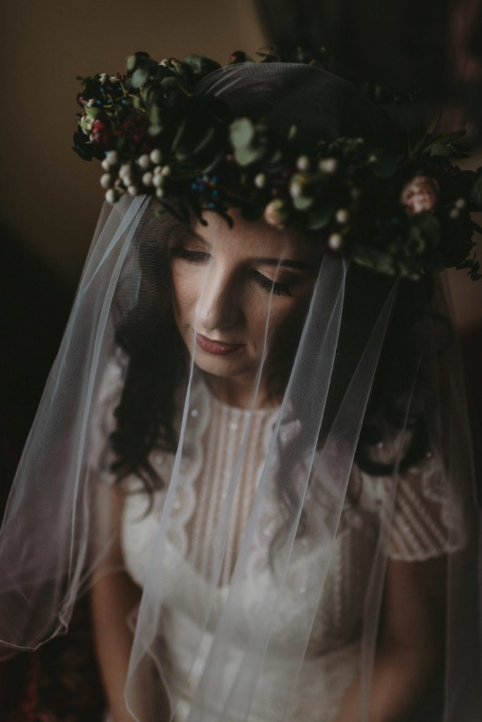 The bride accessorized her look with a veil and a cool floral crown with berries