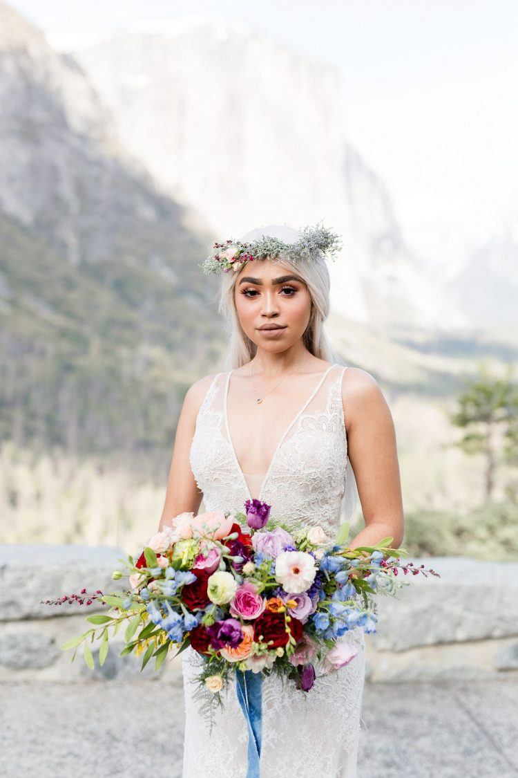 The bride was wearing a lace sheath wedding dress with a covered plunging neckline, a delicate necklace and an ethereal floral crown