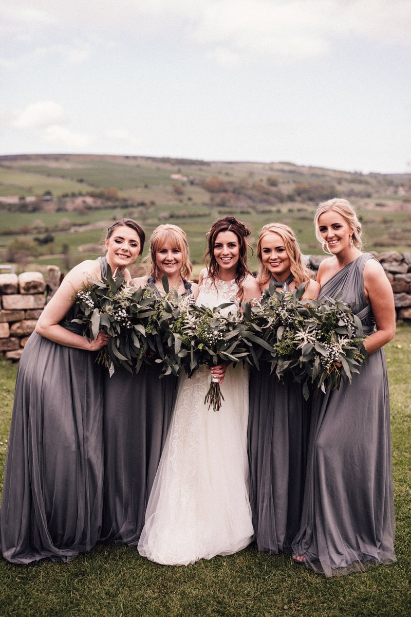 The bridesmaids were wearing mismatching grey maxi dresses and carrying the same greenery bouquets