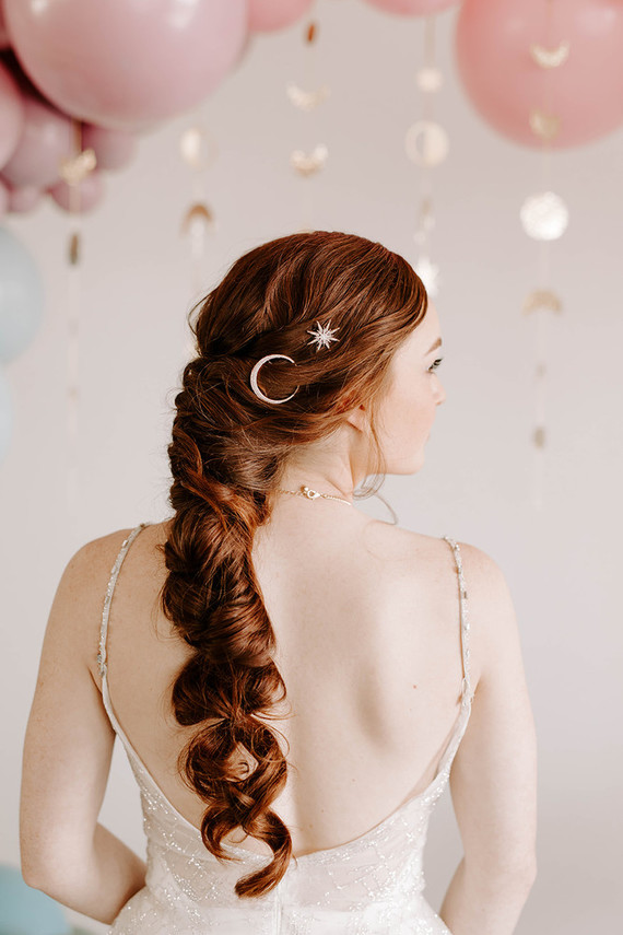 The first wedding dress was a shiny A-line one, with an open back and spaghetti straps, the twisted ponytail was accented with celestial hairpins