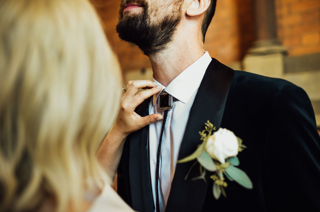 The groom was rocking a black tux and a black bolo tie