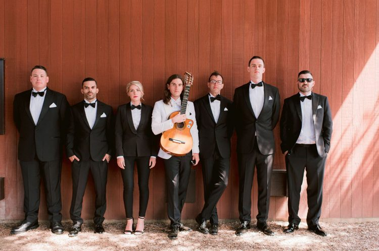 The groom was wearing a white tux and the groom's team was wearing black ones
