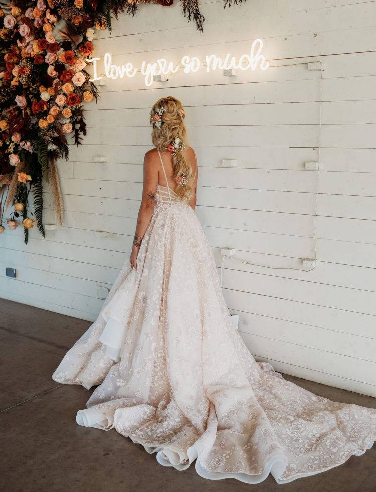 The bride was rocking a flowing voluminous ponytail with blooms