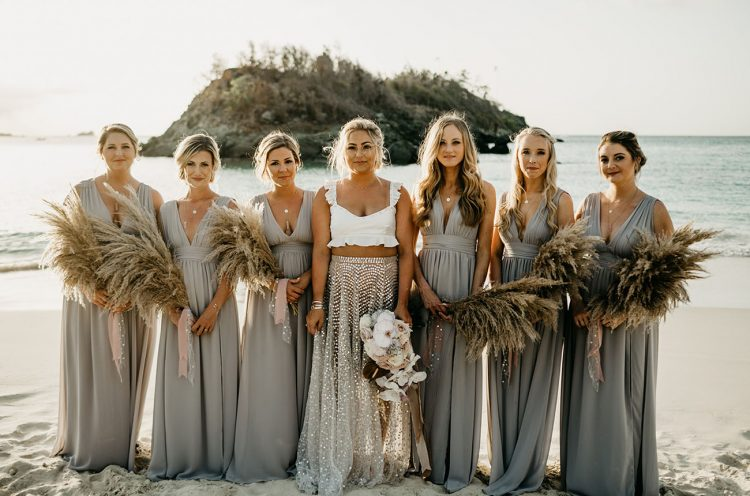 The bride was wearing a white ruffle crop top and an iridescent skirt, the bridesmaids were wearing flowy grey maxi dresses