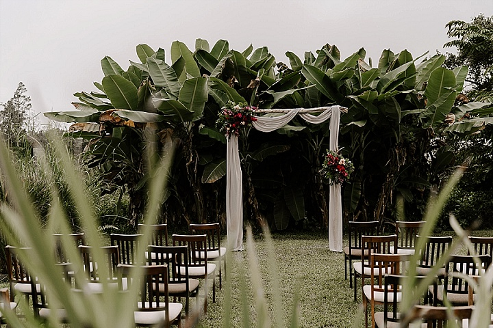 The wedding ceremony space was a tropical grove, with a white fabric arch and bold blooms